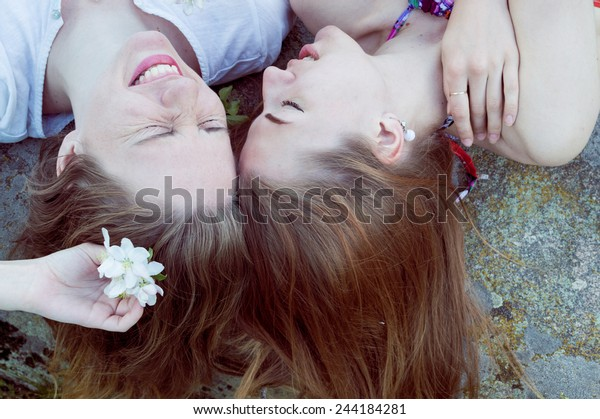 closeup portrait of lying head to head happy girl friends relaxing happy smiling