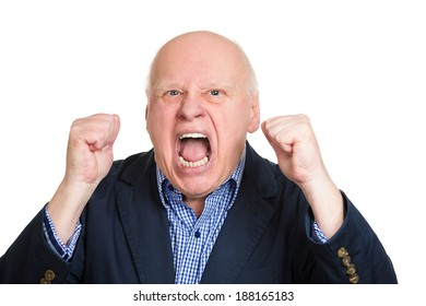 Closeup portrait, mad, upset, senior mature man, funny looking business man, fists in air, open mouth yelling, isolated white background. Negative human emotion facial expression, reaction