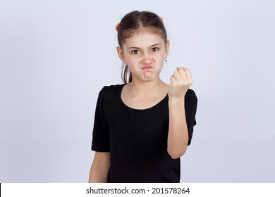 Closeup portrait mad young girl about to have nervous atomic breakdown, fist up in air, angry with someone isolated grey background. Negative human emotion facial expression feeling attitude reaction