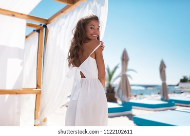 Close-up portrait of magnificent caucasian girl in round pink sunglasses. Lovable long-haired blonde woman enjoying life and having fun at resort.White teeth smile,white dress and blue sky,curly hair