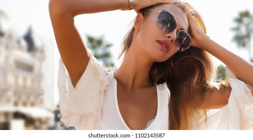 Close-up portrait of magnificent caucasian girl.Lovable long-haired blonde woman enjoying life and having fun at resort.around town in autumn morning. Excited french lady in big glasses expressing hap