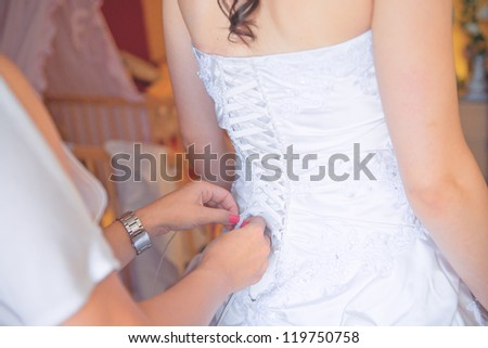 2b7e98a88 closeup portrait of a maid of honor helping the bride with her dress