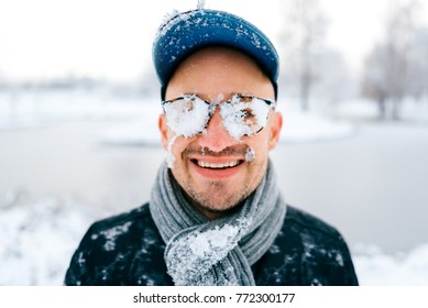 Closeup portrait of male face covered with snow. Crazy cheerful funny comic emotions. Odd bizarre unusual winter idea. Stylish boy wear glasses, hat, scarf. Unique person. Cryotherapy. Frozen skin