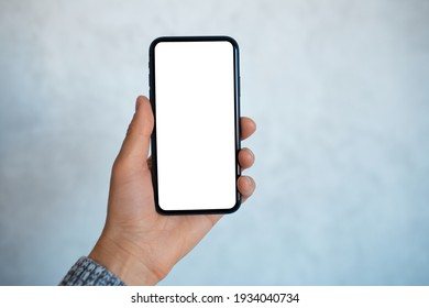 Close-up portrait of male hand, holding a smartphone with mockup, on the background of light grey wall. - Shutterstock ID 1934040734