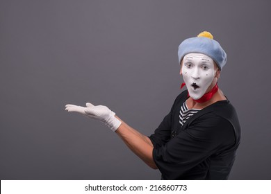 Close-up portrait of male mime with grey hat and white face funny smiling to the camera and panhandling isolated on grey background with copy place