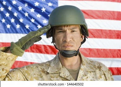 Closeup portrait of a male soldier saluting in front of United States flag