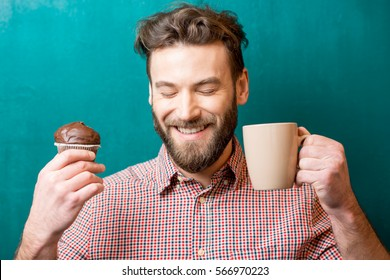 Close-up portrait of a man with chocolate muffin and coffee cup on the green background