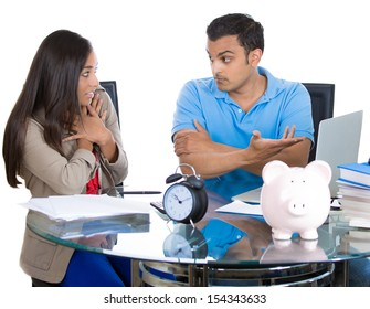 Closeup portrait of man getting angry at woman for spending too much money and pointing at bills on laptop, isolated on white background