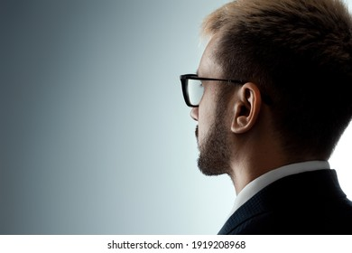 Close-up portrait of a man with glasses sideways in profile looking at the light from the dark. Neutral facial expression, copy space