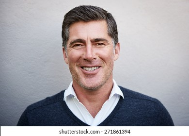 Closeup portrait of a man in his 40s, smiling candidly at the camera while posing outdoors against a textured white wall. His demeanor is pleasant and approachable