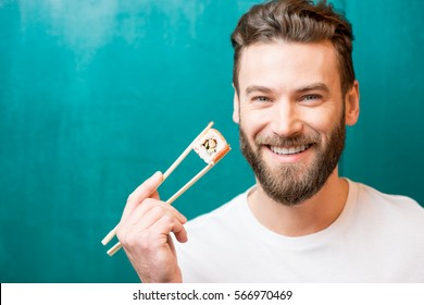 Close-up portrait of a man holding sushi with chopsticks on the green background