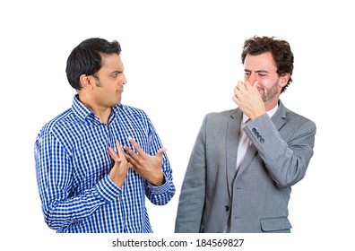 Closeup portrait, man looking at guy closing, covering nose, something stinks, very bad smell, odor. Male asks me? Isolated white background. Negative human emotion, facial expression, feeling