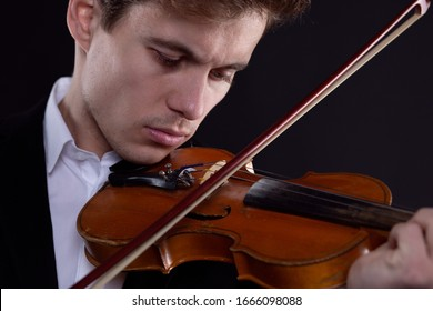 close-up portrait of a man playing the violin in a live performance