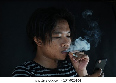 close-up portrait of man smoking cigarette with black background