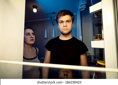 Closeup portrait of man and woman looking in empty refrigerator at night