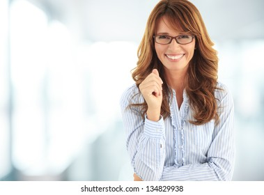 Close-up portrait of a mature business woman smiling in her office