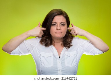 Closeup portrait, mature woman covering plugging ears annoyed by loud noise ignoring someone not wanting to hear their your side story isolated green background. Negative human emotion, expression