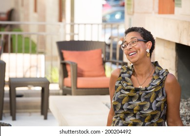 Closeup portrait, mature woman with glasses sitting and laughing, isolated outdoors background with patio furniture