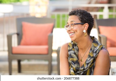 Closeup portrait, mature woman with glasses sitting and smiling, isolated outdoors background with patio furniture