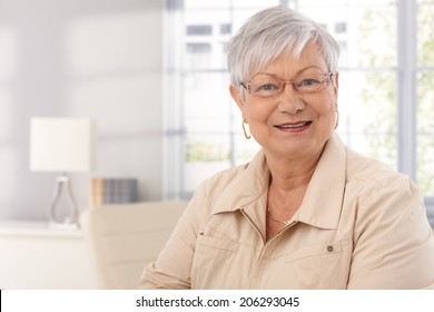 Closeup portrait of mature woman at home, smiling, looking at camera.