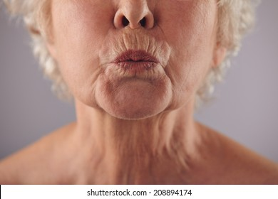 Close-up portrait of mature woman puckering lips against grey background.