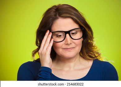 Closeup portrait, mature woman, shy, sad, playing nervously with glasses looking down, feeling guilty, sorry for actions, faults, did wrong, isolated green background. Expression, emotion, reaction