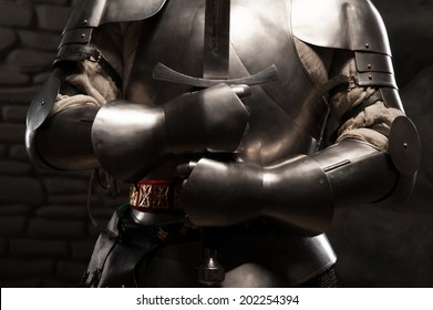 Closeup portrait of medieval knight in armor holding a sword in dark stone wall background