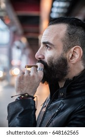 A closeup portrait of a middle aged, Egyptian man smoking alone in the streets of Brooklyn, New York. Shot using ambient light during the spring of 2017.