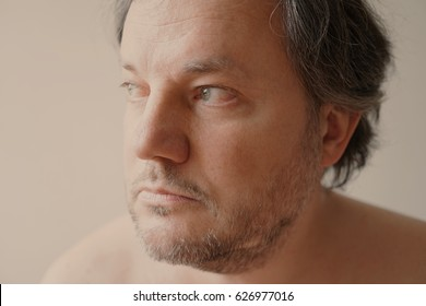 close-up portrait of middle aged man gazing into distance. filtered image with faded vintage effect.