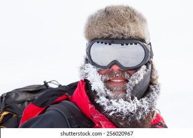 close-up portrait of middle aged men adventurer with frosted beard goggles and fur-cap during winter expedition
