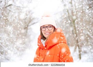 Close-up portrait of middle aged woman wearing hat while standing outdoor and enjoy winter weather in the snwofall.