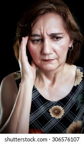 Close-up portrait of a middle aged woman with headache, massaging forehead with her right hand. Black background.