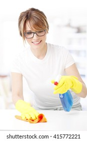 Close-up portrait of middle aged woman holding in her hand a cleaning spray and a tiding rags while cleaning surface at home.