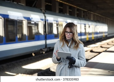 Close-up portrait of middle woman holding in her hands a digital tablet and checking the online schedule while standing at the station.