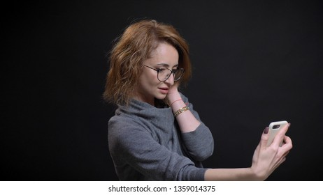 Closeup portrait of middle-aged extravagant red haired female in glasses taking selfies on the phone and posing in front of the camera