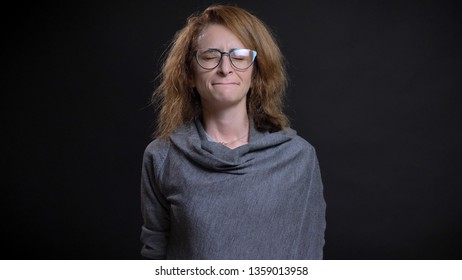 Closeup portrait of middle-aged extravagant redhead female in glasses being depressed and sad in front of the camera
