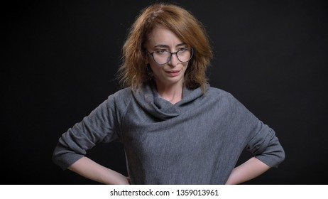Closeup portrait of middle-aged extravagant redhead female in glasses being frustrated and having hands on the hips in front of the camera