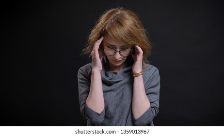 Closeup portrait of middle-aged extravagant redhead female in glasses having a headache and being tired in front of the camera