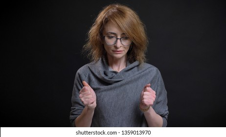 Closeup portrait of middle-aged extravagant redhead female in glasses being worried and nervous clenching her fists in front of the camera