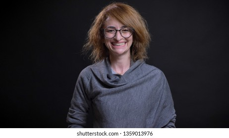 Closeup portrait of middle-aged extravagant redhead female in glasses being happy and smiling cheerfully while looking straight at camera