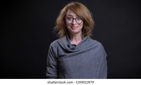 Closeup portrait of middle-aged extravagant redhead female in glasses smiling with excitement and happiness while looking straight at camera