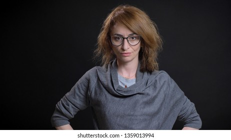 Closeup portrait of middle-aged extravagant redhead female in glasses having hands on the hips and posing while looking straight at camera