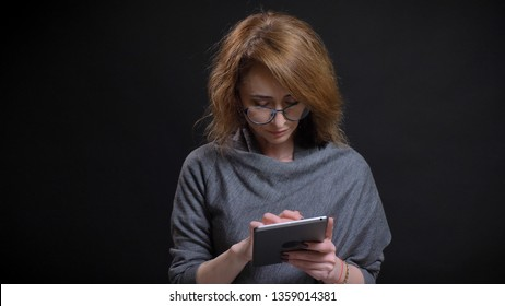 Closeup portrait of middle-aged extravagant redhead female in glasses texting on the tablet in front of the camera with background isolated on black