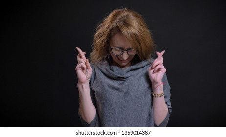 Closeup portrait of middle-aged extravagant redhead female in glasses having her fingers crossed in hope and praying anxiously