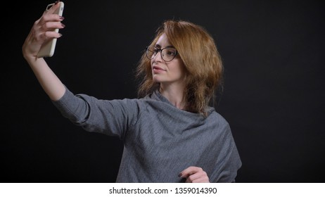 Closeup portrait of middle-aged extravagant redhead female in glasses taking selfies on the phone in front of the camera