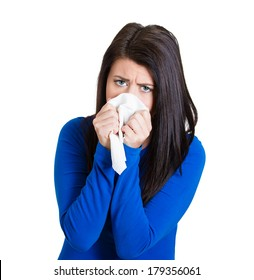 Closeup portrait of a miserable, sick teen woman with allergy, cold, blowing her nose with paper tissue, isolated on white background. Human face expressions. Flu season, vaccination, prevention.