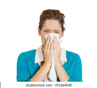 Closeup portrait miserable, sick teen woman with allergy, cold, blowing her nose with paper tissue, isolated white background. Human face expressions, reaction. Flu season, vaccination, prevention.