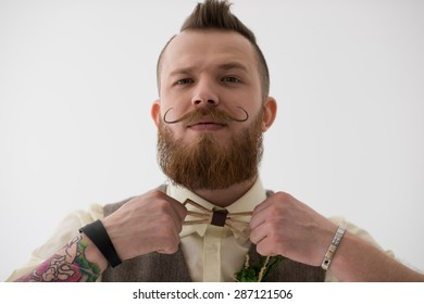 Closeup portrait of modern groom putting on clothes and accessories before his wedding