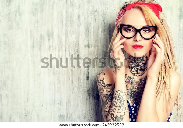 Ritratto in primo piano di una moderna ragazza pin-up con abito vecchio stile a pois e occhiali e dreadlocks moderni. Scatto alla moda. Tatuaggio.
