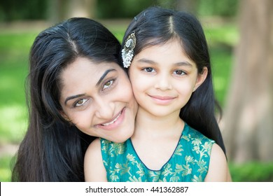 Closeup portrait, mom enjoying time with daughter, isolated outside green trees background
